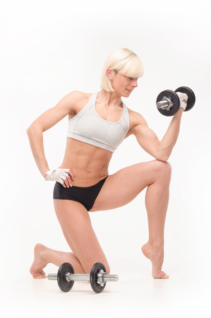only the biceps: female trainer demonstrates the muscles in her arms , and holding dumbbells. isolated on white background