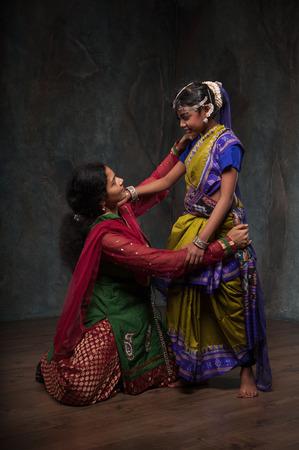 folk culture: happy Indian family , mother instills daughter of folk culture