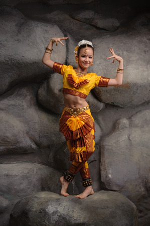 arts culture and entertainment: beautiful little dancer, dressed in a gold national Indian costume Stock Photo
