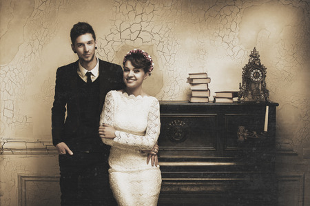 upright piano: photograph of a beautiful young couple , the bride and groom standing near the old upright piano with a candelabra. photo Sepia Stock Photo