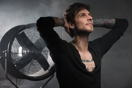 guy with the tattoos looks up with hope. with a dreamy gaze holds both his hands behind head Stock Photo