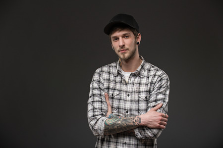pierced ears: guy holds his hands together on his chest. dressed in a plaid shirt and a black cap. his body has tattoos and piercings in the ears