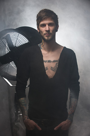 silhouette of a guy in tight pants in front of a big ventilator. Man with tattoos , holding both hands in his pockets Stock Photo
