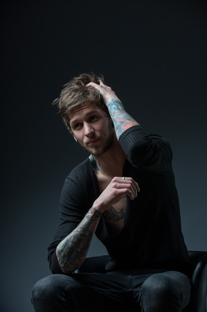 messy hair: guy with messy hair sitting on a chair. With tattoos on both arms and piercings in the ear, on a black background