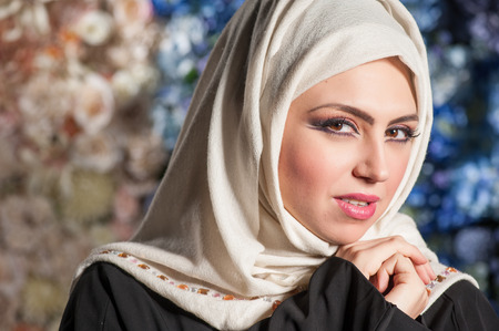 closeup portrait of a young woman in a white headscarf and a black burqa. mysteriously looking at the camera photo