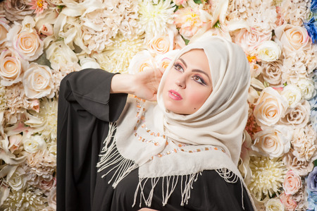Arab woman in a burqa looks with hope. . fresh flowers in the background photo