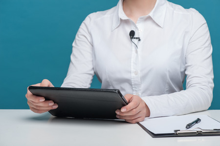 Close up portrait of hands of elegant woman reporter holding the notebook and sitting at the table. There are also pen and folder lying on the table, isolated on a blue background and there is copy place in the left side