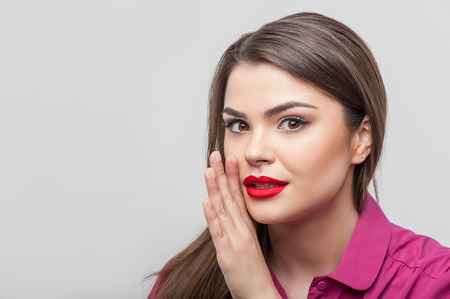 caucasian appearance: Waist up portrait of beautiful woman reporter with Caucasian appearance and red lips, who is looking at the camera mysteriously as if she were trying to tell us a secret while raising her hand near her mouth, isolated on a grey background and there is cop