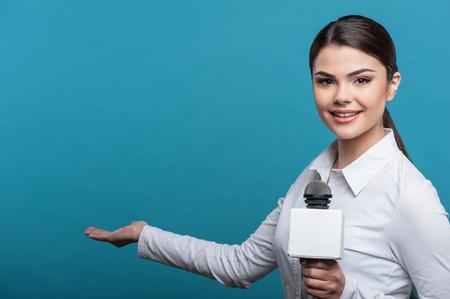 Halve lengte portret van de vrouw verslaggever met lang bruin haar, die interviews en lacht en kijkt naar de camera die de microfoon. Het meisje toont met haar rechterhand opzij, geïsoleerd op een blauwe achtergrond en er is kopiëren plaats in de linker kant