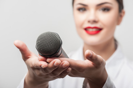 bl: Waist up portrait of beautiful woman reporter with Caucasian appearance with red lips, who is smiling and showing her palms on which the microphone is situated. The palms with microphone are visible on a foreground while the figure of woman is slightly bl