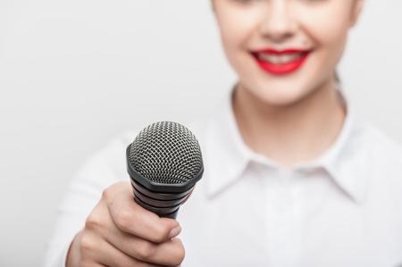 entrevista: Close up retrato de la bella reportera de televisión con la apariencia de raza blanca y los labios de color rojo brillante, que está sonriendo y propone a alguien que le diera la entrevista que sostiene el micrófono, que es visible en el primer plano, mientras que el retrato de la chica es slig