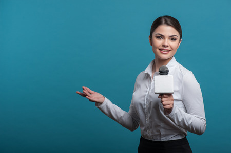 Waist up portrait of elegant woman reporter with brown hair, who interviews and is smiling and looking at the camera holding the microphone and making a gesture with her right hand, isolated on a blue background and there is copy place in the left side
