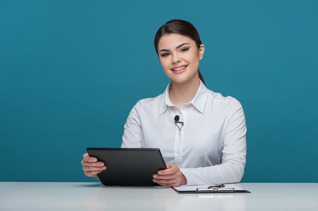 newscast: Waist up portrait of elegant woman reporter with Caucasian appearance, who is telling news and smiling and looking at the camera, sitting at the table and holding the notebook in her arms, isolated on a blue background and there is copy place in the left  Stock Photo