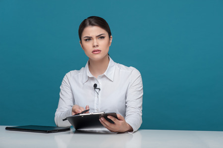 commentator: Waist up portrait of elegant woman reporter of Caucasian appearance, who is looking at the camera questioningly and trying to understand something holding the folder and pen in her arms and sitting at the table, isolated on a blue background and there is