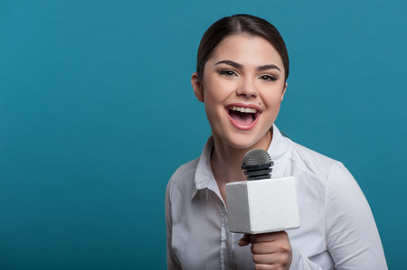caucasian appearance: Waist up portrait of elegant young woman reporter, who interviews and is smiling at the camera speaking about something very emotionally and holding the microphone. She has Caucasian appearance, isolated on a blue background and there is copy place in the