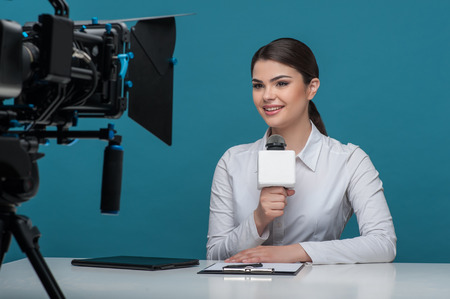 Waist up portrait of elegant woman reporter with brown hair, who is telling the news and smiling looking at the camera while sitting at the desk and holding the microphone, the camera is visual on a foreground, isolated on a blue background