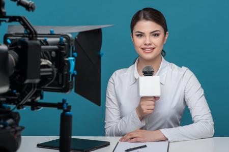 Taille portret van elegante vrouw reporter met blanke verschijning, die lacht en kijkt recht naar de tweede camera, terwijl de eerste camera is visueel op een voorgrond en ze houdt de microfoon tijdens de vergadering op de tafel, die op ab