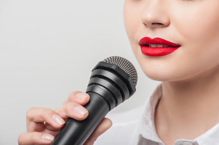 commentator: Close up portrait of beautiful woman reporter, who is holding the microphone and talking into it slightly smiling. She has Caucasian appearance and bright red lips, isolated on a grey background and there is copy place in the left side