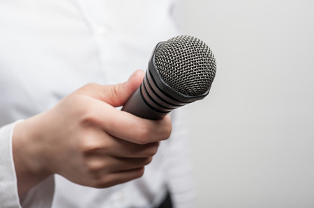 Close up portrait of microphone, which is hold by woman tv reporter and visible on the foreground. The girl is waiting for the answer of someone and the figure of her is slightly blurred, isolated on a grey background and there is copy place in the right  photo