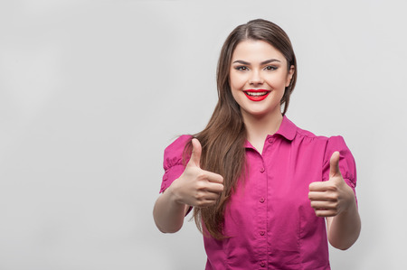 caucasian appearance: Everything is okay. Waist up portrait of happy beautiful young woman reporter with Caucasian appearance and red lips, who is smiling and raising her thumbs up as if everything were fine, isolated on a grey background and there is copy place in the left si Stock Photo