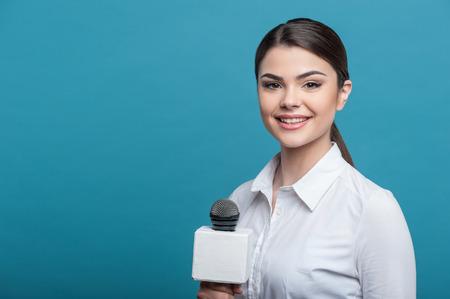 entrevista: Cintura para arriba retrato de reportero mujer elegante, que entrevista y está sonriendo y mirando a la cámara sosteniendo el micrófono. Ella tiene el pelo largo de color marrón y una blusa blanca, aislado en un fondo azul y no copiar lugar en el lado izquierdo Foto de archivo