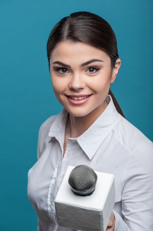 Half length portrait of elegant woman reporter, who is holding the microphone and proposes someone to give her the interview and waiting for the answer smiling and looking at the camera and holding the microphone. She has long brown hair and a white blous