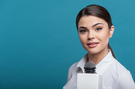 caucasian appearance: Waist up portrait of elegant woman reporter with Caucasian appearance, who is holding the microphone looking attentively at the camera and waiting for the answer. She has long brown hair and a white blouse, isolated on a blue background and there is copy
