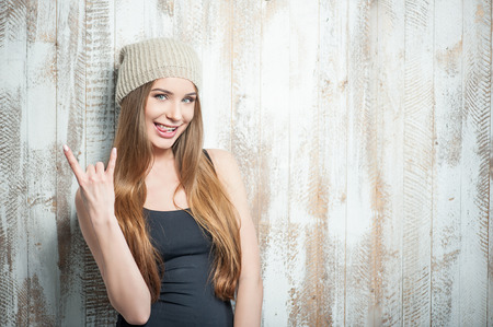 Waist up portrait of beautiful hipster girl with nice hat, who is showing a gesture that symbolizes adoring rock and metal, impertinently smiling and grimacing showing her tongue expressing all her coolness, isolated on a white background and there is cop Stock Photo