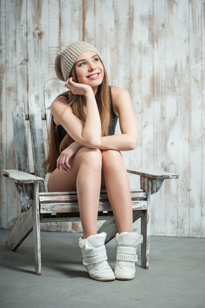 looking towards camera: Close up portrait of cheerful hipster girl with cool woven hat, who is sitting on the chair dreamily smiling and looking towards, her hand is propping up her head, isolated on a white background Stock Photo