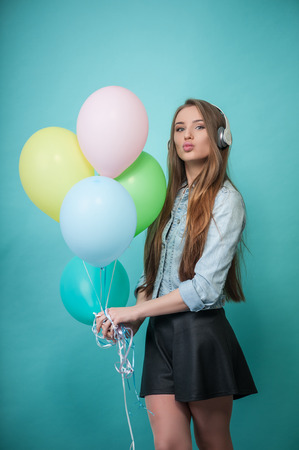 caucasian appearance: Full length portrait of beautiful hipster girl with Caucasian appearance, who is standing while holding varicolored balloons in her hand, wearing headphones listening to music looking at the camera mysteriously and sending blow kiss, isolated on blue back