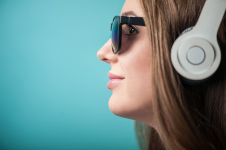 close p: Close up portrait of profile of beautiful hipster girl with brown hair, who is listening to music thoughtfully and mysteriously and looking to the left. She has black sunglasses and headphones on her head, isolated on a blue background and there is copy p