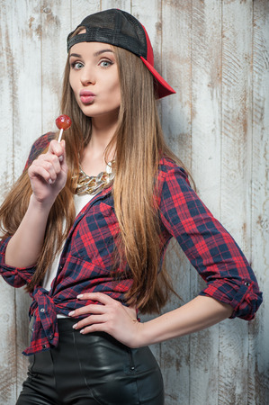 kissing mouth: Cheerful Hipster woman with hat and candyWaist up portrait of pretty hipster girl with Caucasian appearance, who is holding lollipop near her mouth and makes her lips in such way as if she kissed someone looking at the camera. She is wearing cap, isolated