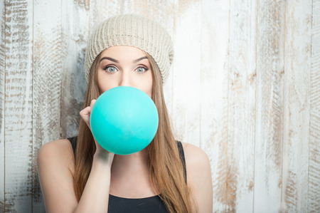 Pretty hipster woman is inflating colored balloonWaist up portrait of cheerful hipster girl with Caucasian appearance, who is standing near the white wall and is blowing balloon diligently and looking at the camera amazedly, isolated on a white background Stock Photo
