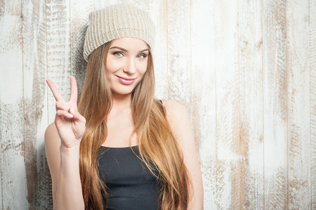 caucasian appearance: Waist up portrait of pretty hipster girl with Caucasian appearance, who is standing near the white wall and positively showing the gesture that symbolizes peace in the world and gently smiling. She is wearing a nice woven hat, isolated on a white backgrou Stock Photo