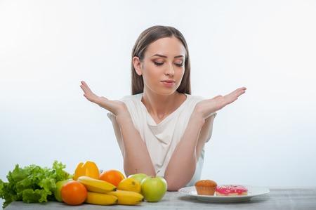 柏木は、食欲と魅惑的な不健康なドーナツを見ています。彼女は身振りで示すことは、何をするかは知らない。白い背景に分離