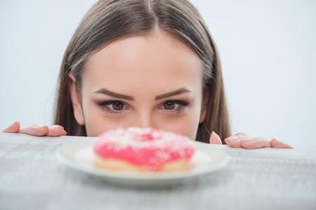 pastel: La muchacha hermosa est� mirando rosquilla enfermiza con el apetito en una mesa. Aislado en un fondo blanco