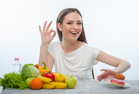 fight hunger: Beautiful woman is pushing the plate with donuts aside. Isolated on a white background