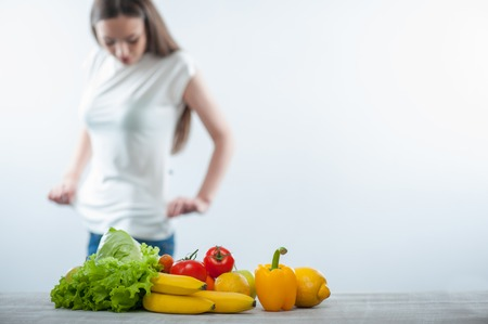 sighting: Cheerful healthy woman is sighting herself carefully. Focus on healthy food. Isolated on a white background