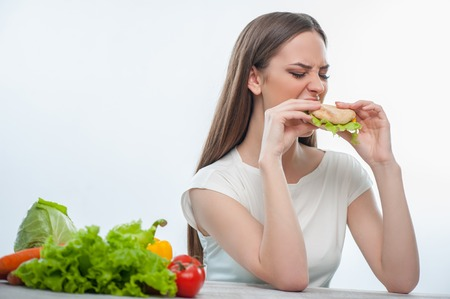 Pretty woman is biting harmful hamburger with disgust. Isolated on a white background Stock Photo