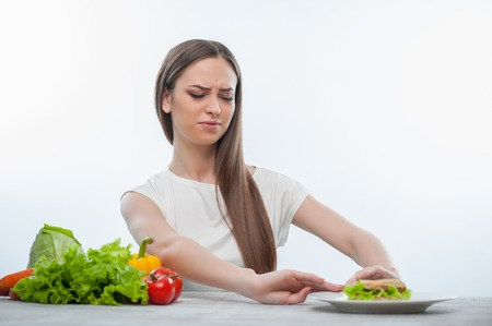refusing: Pretty woman is refusing to eat unhealthy hamburger. Isolated on a white background Stock Photo