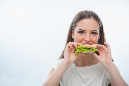 空腹のきれいな女性は徐々 にハンバーガーを噛んでいます。白い背景に分離