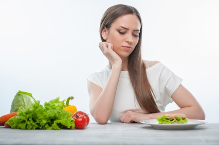 aversion: Beautiful girl is looking at hamburger with aversion. Isolated on a white background Stock Photo