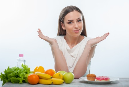 no mistake: Pretty woman cannot make a decision what she should eat. Isolated on a white background