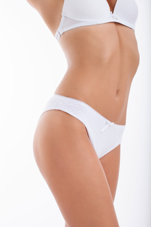 Close up of waist of healthy woman presenting her slim figure in white underwear. Isolated on white background