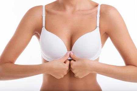 senos: Cierre de mama de la mujer del ajuste a desabrochar su sujetador blanco en frente de su cuerpo. Aislado en el fondo blanco