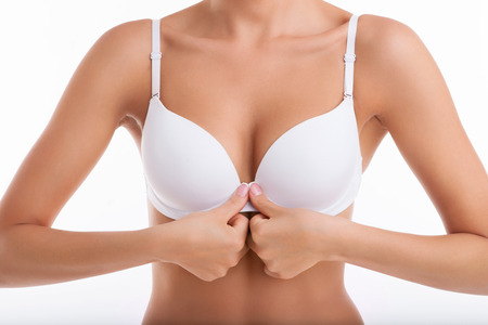 big breast: Close up of breast of fit woman unbuttoning her white bra in front of her body. Isolated on white background Stock Photo