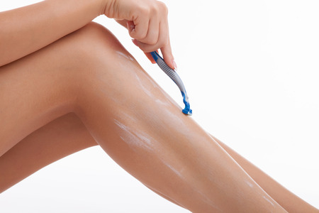 legs  white: Close up of legs of healthy girl shaving her legs carefully. She has shaving cream on her legs. Isolated on white background