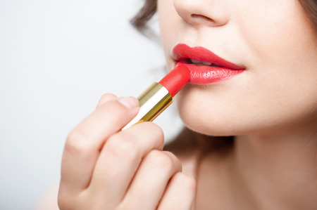 nude young woman: Close up portrait of attractive girl rouging her lips. She is holding red lipstick. Her mouth is gently open. Isolated on grey background