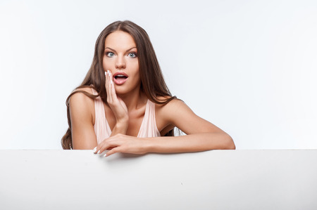 private parts: Attractive woman is leaning on part of white wall. She is looking through it with shock. Isolated on background and there is copy space in right side