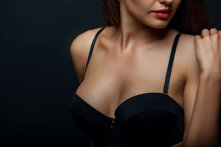 nude breast: Close up of breast of attractive woman presenting her black bra. She is touching her shoulder gently. Isolated on black background and there is copy space in left side Stock Photo